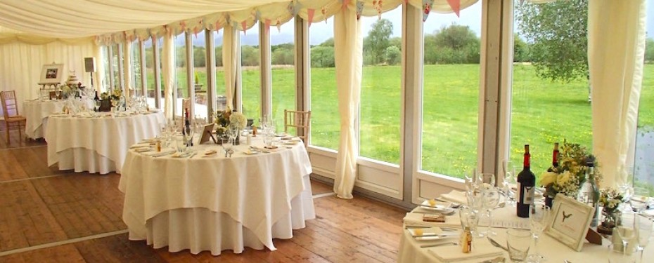 Wedding Marquee with suspended wood flooring and circular tables